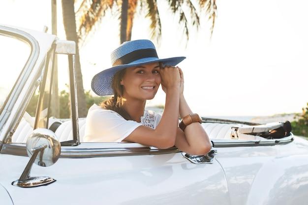 Giovane donna felice e retro automobile convertibile accanto alla spiaggia alla città di varadero