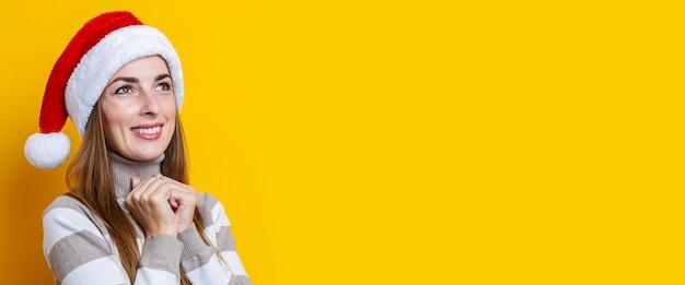 Felice giovane donna in cappello di babbo natale su uno sfondo giallo. bandiera.
