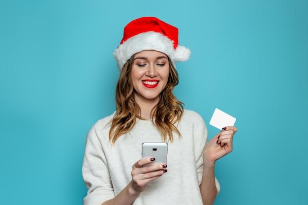 Giovane donna felice in cappello della santa che sorride e che tiene la carta di credito ed esamina il telefono cellulare isolato sulla parete blu
