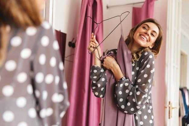 Felice giovane donna shopaholic guardando specchio.