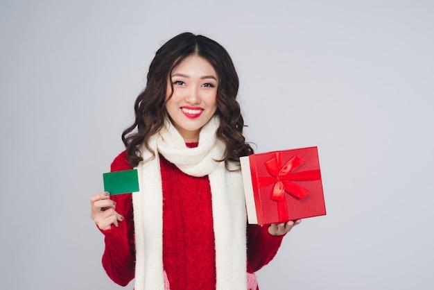 Acquisto felice della giovane donna con la carta di credito e contenitore di regalo della tenuta su natale isolato.