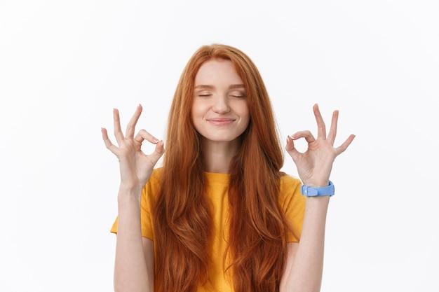 Giovane donna felice che mostra segno giusto con le dita un ammiccante