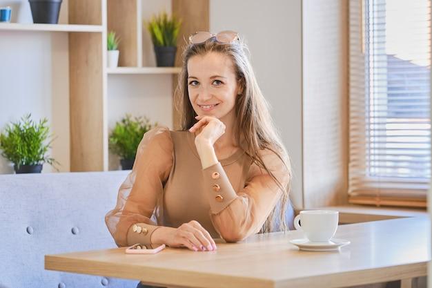 Felice giovane donna si siede nella caffetteria, avendo pausa caffè