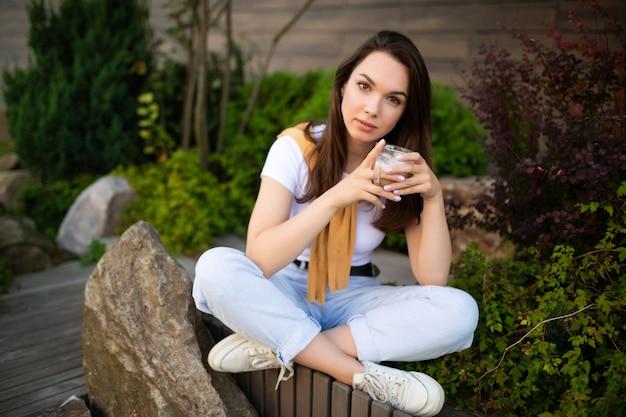 Felice giovane donna seduta in un bellissimo parco e bere latte piccante.