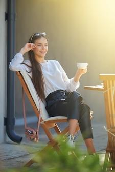 Felice giovane donna seduta sulla terrazza del caffè in una giornata di sole e bere caffè. donna che gode del primo sole primaverile all'aperto.