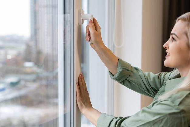 Felice giovane donna stare vicino alla finestra respirare aria fresca esercizio di stiramento in camera da letto, sorridente ragazza millenaria felicissima benvenuto nuova mattina di sole a casa o in hotel, ottimismo, concetto di felicità