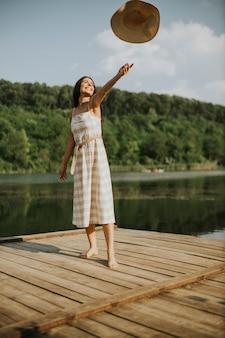 Felice giovane donna in piedi sul molo di legno al lago calmo