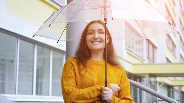 Una giovane donna felice sta sotto un ombrello trasparente sotto la pioggia sullo sfondo di un condominio
