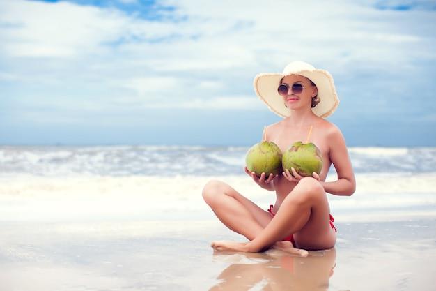 Felice giovane donna in cappello di paglia in spiaggia con una bevanda al cocco