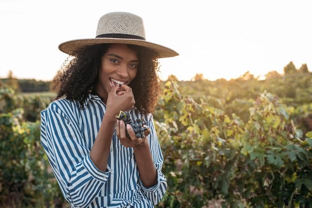 Giovane donna felice in un cappello di paglia che mangia l'uva in una vigna