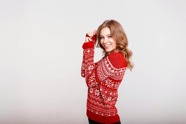 Felice giovane donna in elegante maglione rosso vintage con ornamento su uno sfondo grigio