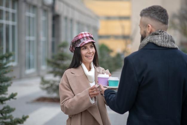 Felice giovane donna prendendo una tazza di caffè mentre guarda il suo fidanzato
