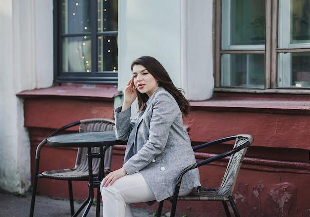 Felice giovane donna o ragazza adolescente seduto in terrazza caffè strada di città e sognare