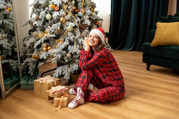 Giovane donna felice che getta un regalo vicino all'albero di natale. lei seduta vicino a regali e regali. colori di tendenza fortuna gold e tidewater green.