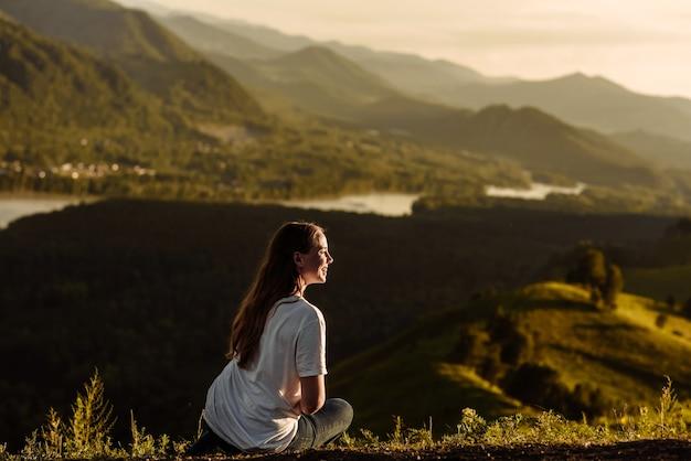Turista felice della giovane donna si siede e sorride sullo sfondo di una valle e di un fiume di montagna