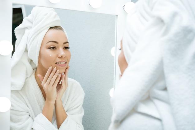 Una giovane donna felice in un asciugamano davanti a uno specchio applica la crema sul viso, un concetto di cura della pelle a casa