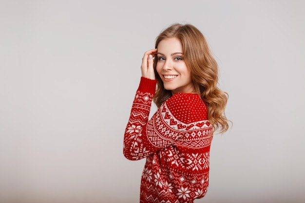 Giovane donna felice in un maglione rosso di inverno di modo alla moda su uno sfondo grigio