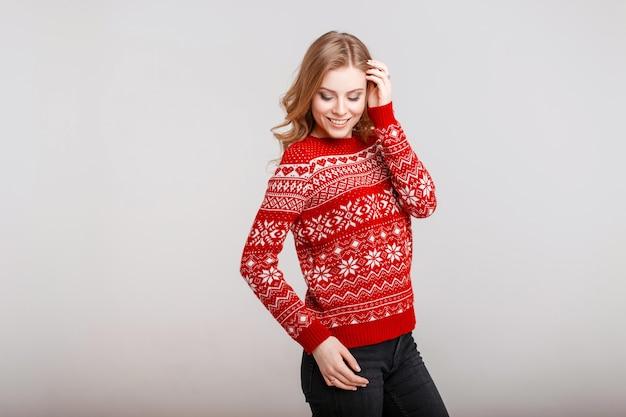 Felice giovane donna in un maglione rosso alla moda con stampa su uno sfondo grigio al chiuso
