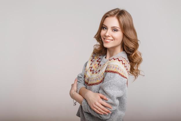 Felice giovane donna in un maglione elegante alla moda su uno sfondo grigio