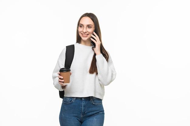 Studente universitario felice della giovane donna con lo zaino ed i libri che parlano sul telefono cellulare isolato sul muro bianco