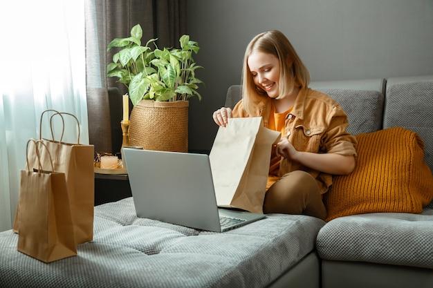 Felice giovane donna fa disimballaggio ordini online merci o cibo shopping online ordinando consegna ragazza adolescente rilassarsi sul divano considerando gli acquisti con laptop mock up sacchetti di carta