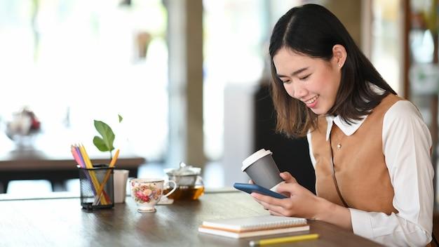 Felice giovane donna che utilizza smartphone navigando sui social media e bevendo caffè in ufficio.