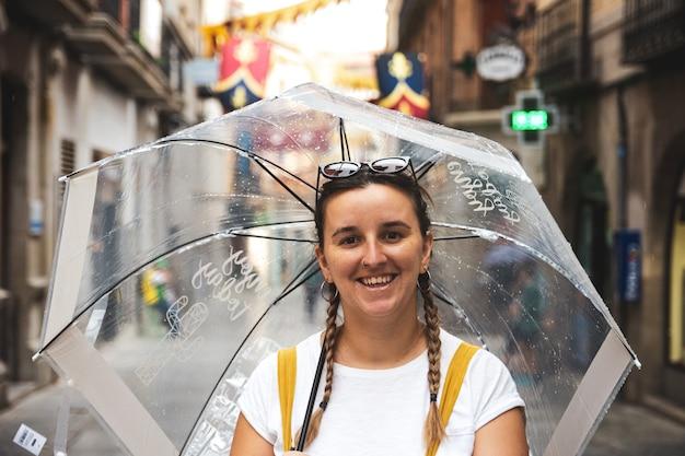 Felice giovane donna che cammina per la città con il suo ombrello in una giornata piovosa.