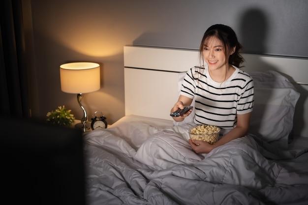 Felice giovane donna che guarda la tv su un letto di notte