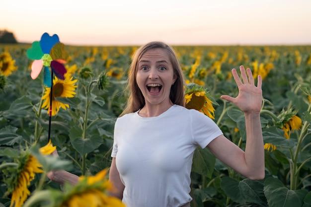 Felice giovane donna agitando la mano sul campo di girasole con il giocattolo del mulino a vento