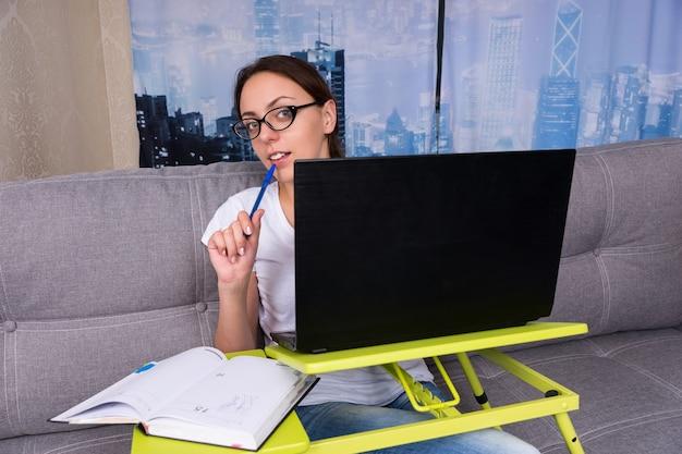 Felice giovane donna con gli occhiali che sbircia dietro il laptop mentre lavora e fa i suoi affari da casa con in mano una penna