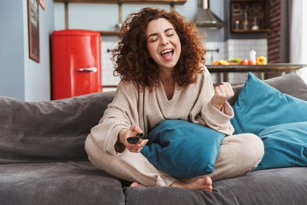 Felice giovane donna che indossa abiti da casa seduta sul divano in appartamento e tenendo il telecomando