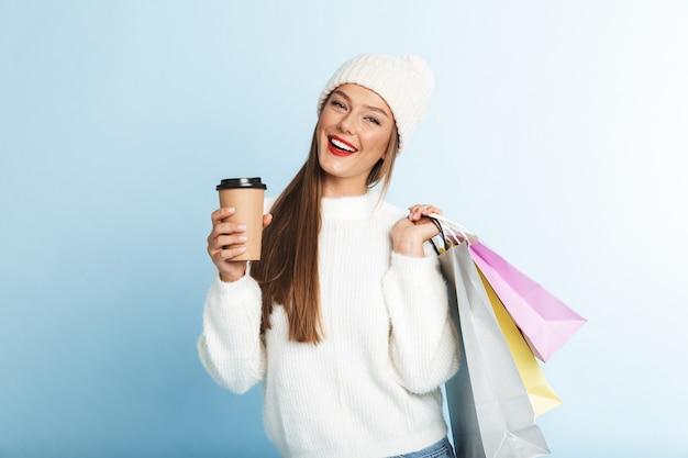 Felice giovane donna che indossa un maglione, portando borse della spesa, bere caffè
