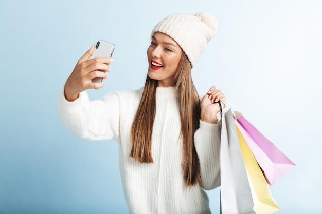 Felice giovane donna che indossa un maglione, portando le borse della spesa, tenendo il telefono cellulare, prendendo un selfie