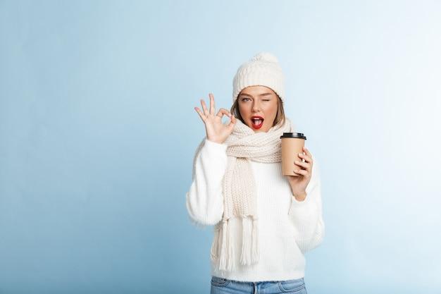 Felice giovane donna che indossa un maglione e cappello, tenendo il caffè da asporto, gesto ok