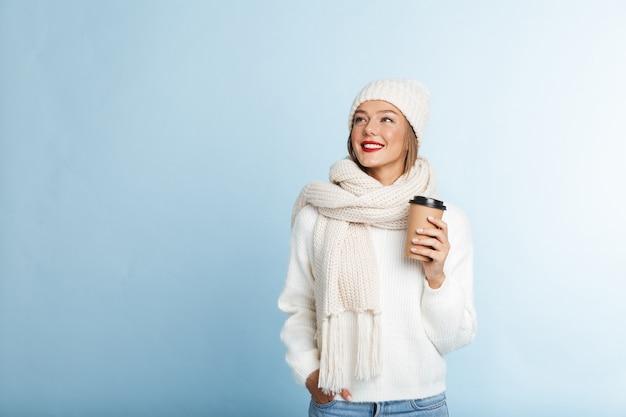Felice giovane donna che indossa un maglione e cappello, tenendo il caffè da asporto