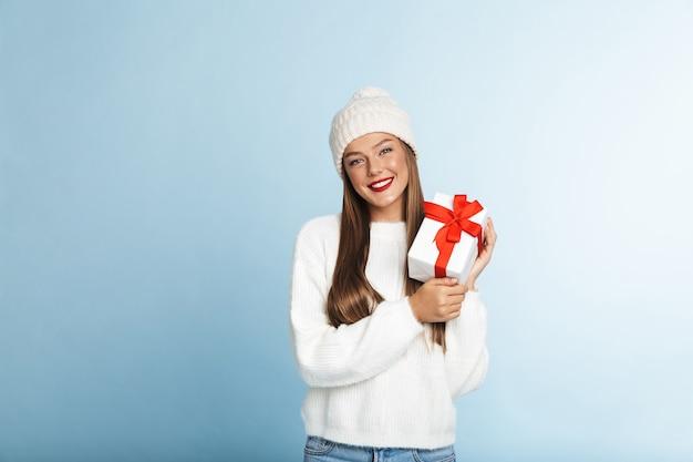 Felice giovane donna che indossa un maglione tenendo presente la casella