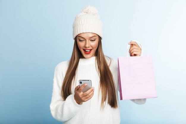 Felice giovane donna che indossa un maglione mostrando vuoto shopping bag, utilizzando il telefono cellulare