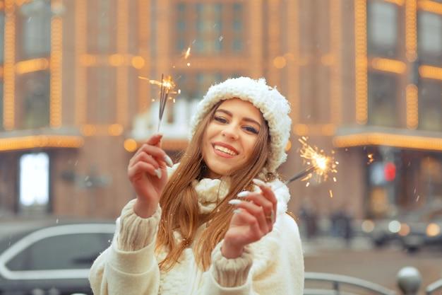 Felice giovane donna indossa un cappello e un cappotto a maglia bianchi che si divertono con le stelle filanti per la strada decorata a natale