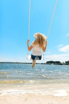 Felice giovane donna in maglietta bianca e pantaloncini di jeans che oscillano in alto vicino al lago. donna gioiosa con capelli ricci biondi che trascorre i fine settimana all'aria aperta.