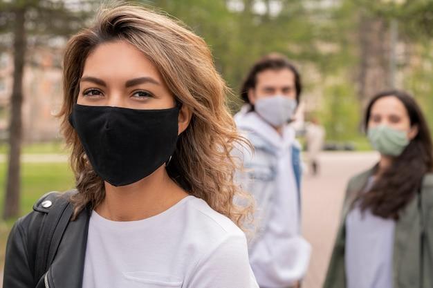 Felice giovane donna in t-shirt bianca, giacca di pelle e maschera protettiva in tessuto nero