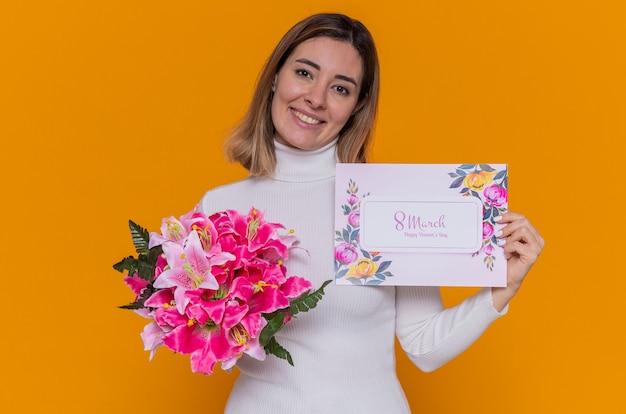 Felice giovane donna in dolcevita bianco azienda biglietto di auguri e bouquet di fiori