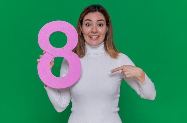 Felice giovane donna in bianco dolcevita tenendo il numero otto puntato con il dito indice a sorridere allegramente per celebrare la giornata internazionale della donna marzo