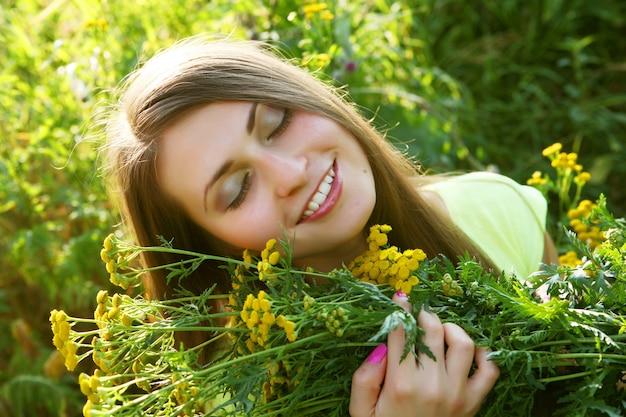 Felice giovane donna e fiori selvatici.