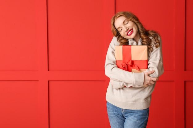 Felice giovane donna in abiti invernali e con un regalo di natale sullo spazio colore