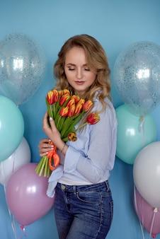 Felice giovane donna con bouquet in mano e palloncini di elio