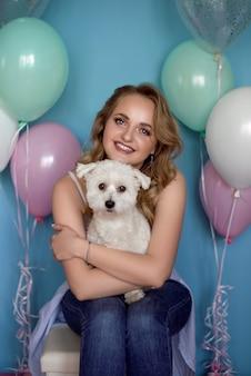 Felice giovane donna con bouquet con cucciolo ed elio palloncini
