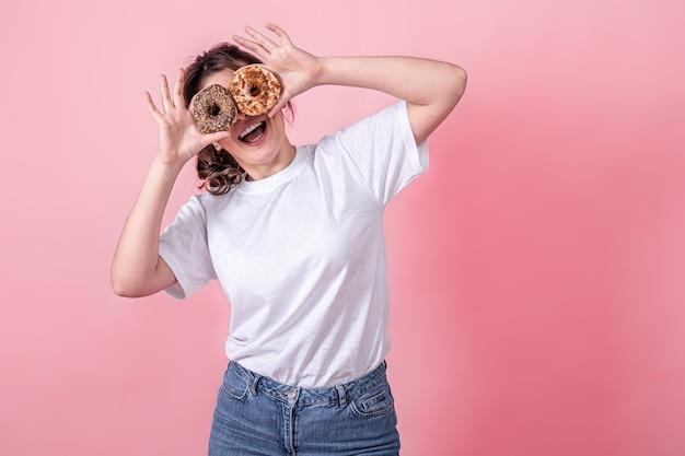 La giovane donna felice con le ciambelle nelle sue mani sorride tiene le ciambelle rosa vicino ai suoi occhi le sue mani
