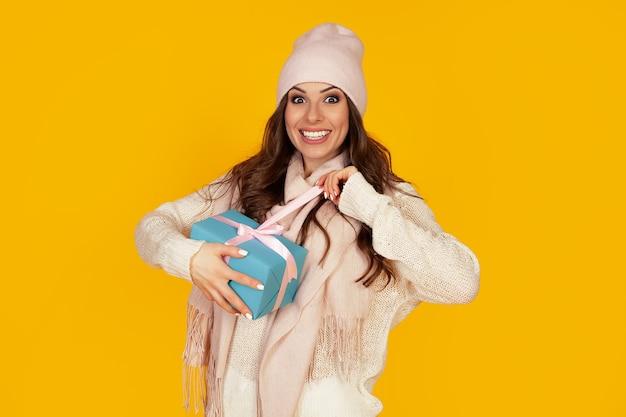 Felice giovane donna con la bocca aperta che apre una confezione regalo del regalo di natale, la ragazza guarda nella confezione regalo e ride di felicità. il concetto di regali e sorprese per il nuovo anno e il natale.