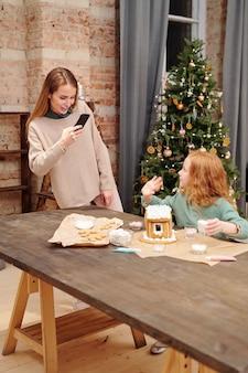 Giovane donna felice con lo smartphone che cattura foto della sua piccola figlia sveglia agitando la mano mentre prepara il dessert di natale da tavola