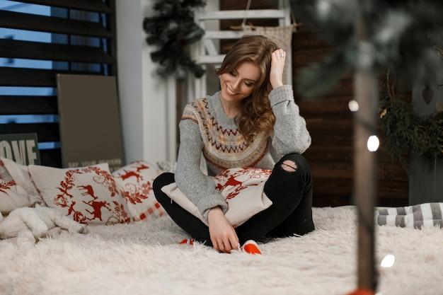 Felice giovane donna con un sorriso in un maglione vintage con un cuscino appoggiato sul letto